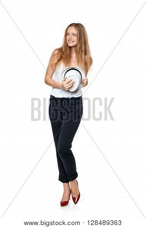 Beautiful slytish woman in full length laughing smiling to the side at blank copy space and holding fedora hat, over white background