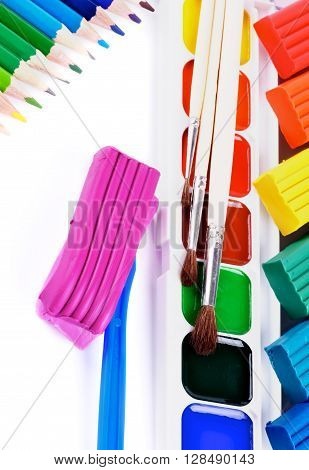 Arrangement of Watercolor Paints Paint Brushes Multi Colored Clay and Colored Pencils isolated on White background