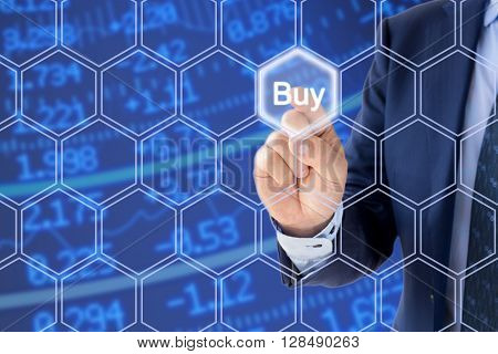 Businessman in a blue suit pressing the buy button an a hexagon grid in front of a stock ticker wall