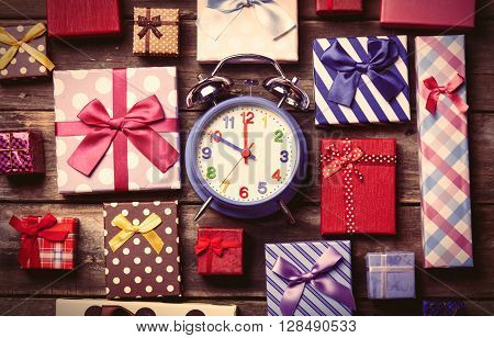 colorful gifts and blue clock on the brown wooden table