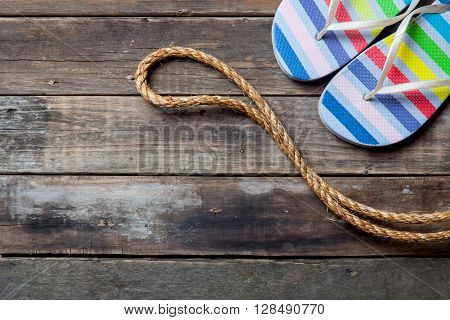 colorful sandals and rope on the brown wooden background