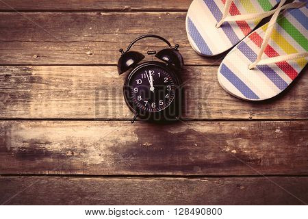 photo of the black clock and colorful sandals on the brown wooden background
