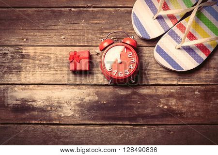 photo of the red clock gift and colorful sandals on the brown wooden background