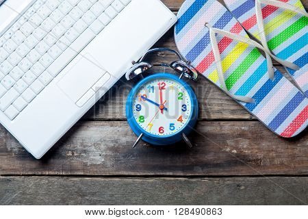 photo of the blue clock laptop and colorful sandals on the brown wooden background