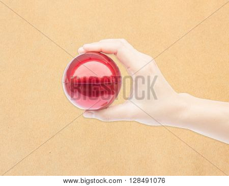 Hand on shiny red ball on brown background stock photo