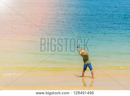 Young boy fishing rod on sunny beach