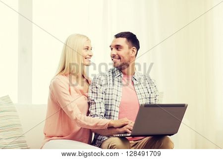 love, family, technology, internet and happiness concept - smiling happy couple with laptop computer at home