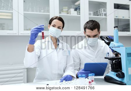science, chemistry, technology, biology and people concept - young scientists with test tube and microscope making research in clinical laboratory