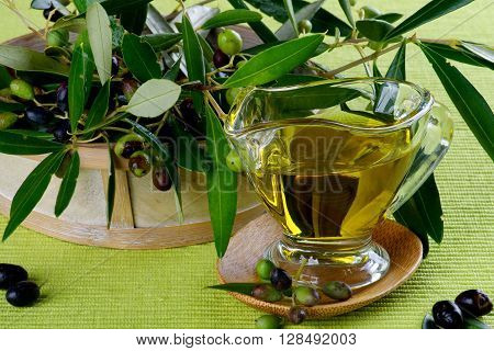 Olive Oil in Glass Gravy and Raw Green and Black Olives with Leafs in Wooden Bowl closeup on Green Textile background