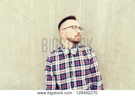 people, style, technology, leisure and lifestyle - happy young hipster man with headphones over concrete wall on city street
