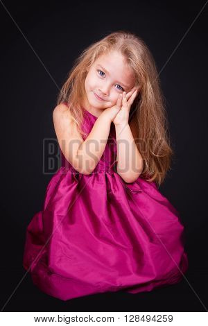 Little cute girl sitting on the floor in a pink dress on a black background in the studio