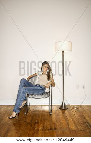 Attractive young woman slouching in a silver chair next to a floor lamp. She is looking towards the camera. Vertical shot.