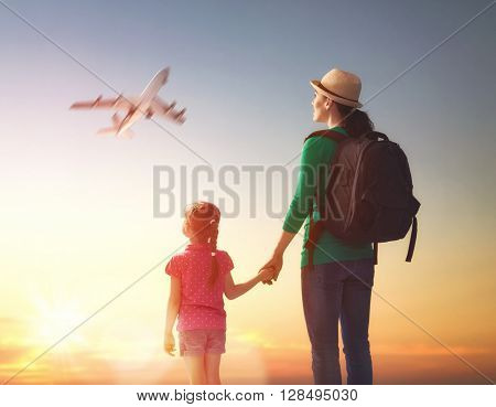 happy family at sunset. mother and her child daughter looking at the flying plane in the sky.