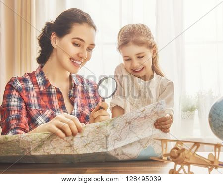 Go on an adventure! Happy family preparing for the journey. Mom, dad and daughter study the map and choose a route of travel.