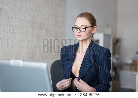 Sexy secretary in formal dress undressing in office online flirt