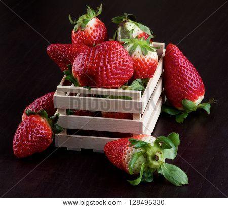 Arrangement of Fresh Ripe Strawberries in Wooden Box closeup on Dark Wooden background