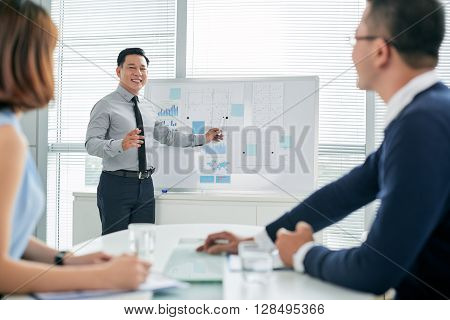 Smiling Asian businessman conducting presentation in front of colleagues