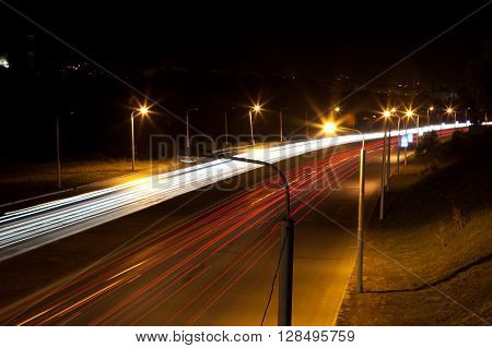 Highway road at night with light traces
