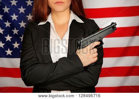 Woman holding gun on USA flag background