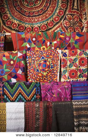 Colorful Mexican patterned fabric hanging on a rack. Vertical shot.