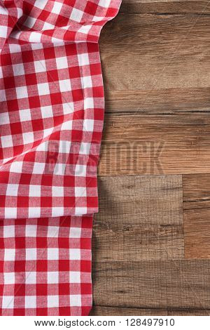 Red and white checkered table cloth on a wood table with copy space, vertical format.