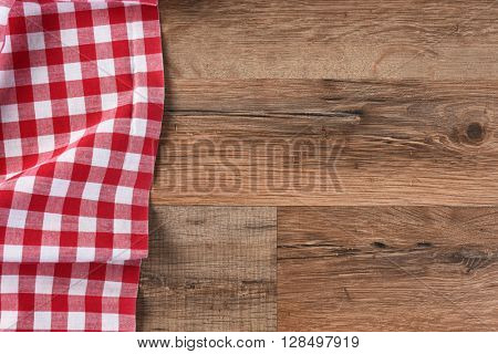Checkered table cloth on a wood table with copy space, horizontal format.