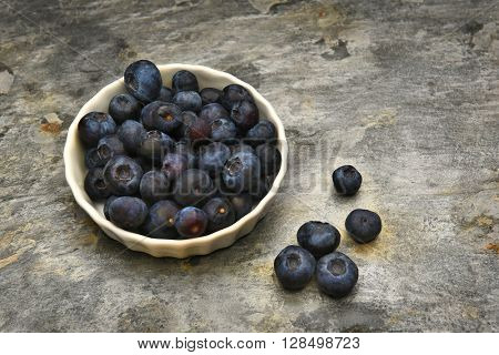 A ramekin filled with fresh ripe blueberries on a slate table top, with loose berries scattered on the table.