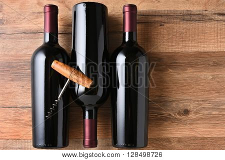 Top view of three red wine bottles on a wood table with an old fashioned corkscrew.