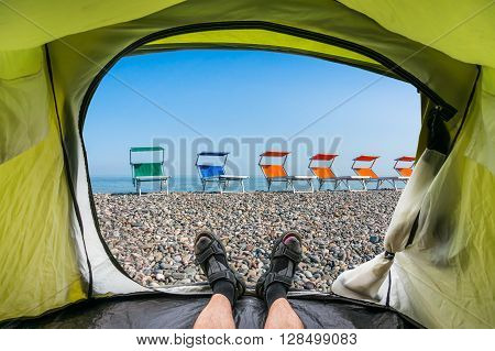 View from inside a tent on the colorful beach chairs on the shingle beach near sea