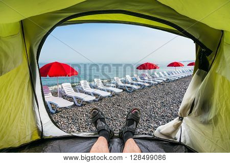 View from inside a tent on the sun loungers on a beach and red umbrella