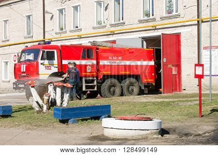 LODEYNOJE POLE, RUSSIA - MAY 2TH, 2016: Unidentified firefighters washing their fire truck near the garage