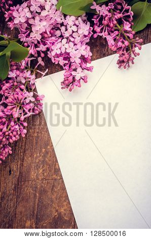 Bunch of lilac on brown wooden old table with blank paper page empty space for text. Lilac vertical background. Happy Mothers Day. Mother's Day greetings card. Mothers Day gift. Toned image.