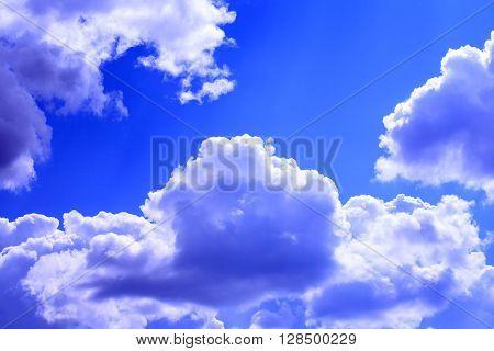 Nature background. Few big white clouds in blue sky