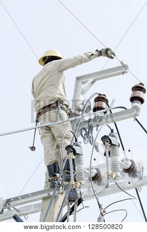 One electrician is repairing wire on electric power pole.