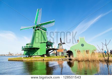 Zaanse schans, Holland - April 1, 2016: Windmill in Zaanse Schans, traditional village in Netherlands, North Holland against blue cloudy sky