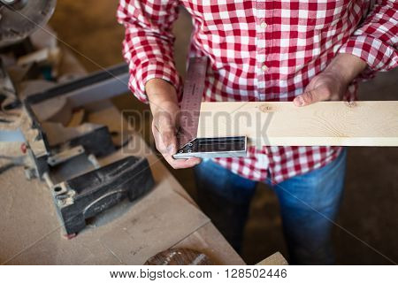 master carpenter measure wooden board with the help of the corner line workshop joiner's shop tools handmade concept close-up measurement