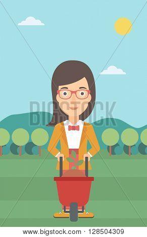 Woman with plant and wheelbarrow.