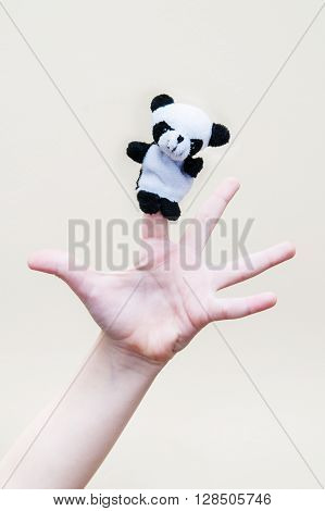 Children's palm with a toy panda on the index finger