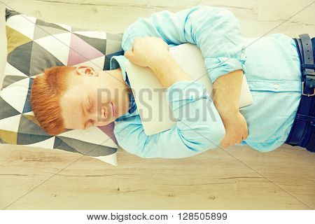Young tired man with laptop sleeping on the floor