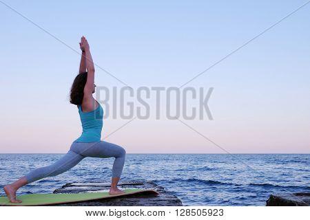 Young woman practicing yoga at seashore