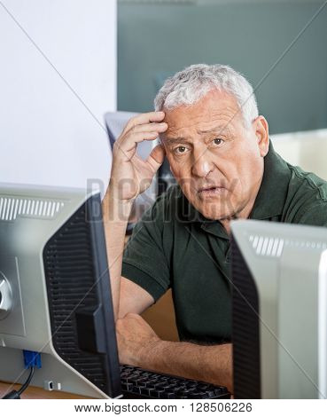 Shocked Senior Man At Computer Desk In Classroom
