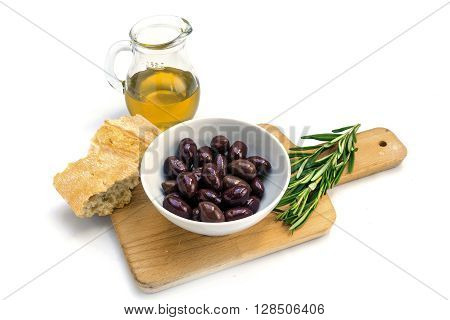 Kalamata black olives in a white bowl olive oil bread and rosemary garnish on a kitchen board isolated on a white background