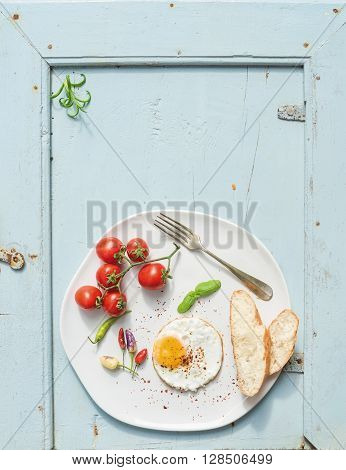 Breakfast set. Fried egg, bread slices, cherry tomatoes, hot peppers and herbs on white ceramic plate over light blue wooden backdrop, top view, copy space