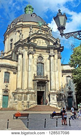 LVIV, UKRAINE - JULY 17, 2015: Unidentified people are walking near Dominican Cathedral in the beautiful summer day in Lviv, Ukraine. It was originally built as the Roman Catholic church of Corpus Christi