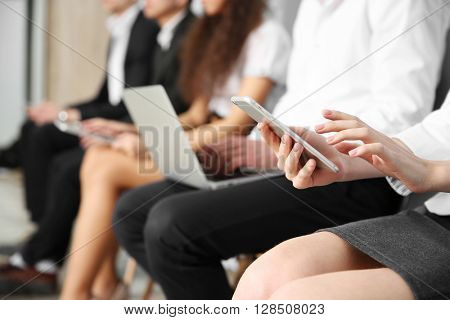 Group of people sitting with devices indoors