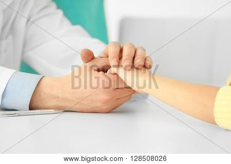 Doctor's hands touching patient's, close-up