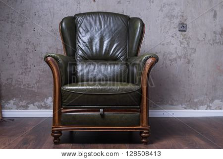 Green Leather Armchair In Front Of The Wall