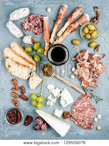 Cheese and meat appetizer selection or wine snack set. Variety of  cheese, salami, prosciutto, bread sticks, baguette, honey, grapes, olives, sun-dried tomatoes and pecan nuts over grey concrete textured backdrop, top view, vertical