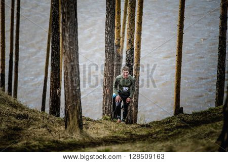 Ekaterinburg Russia - April 24 2016: young male athlete running uphill around tall pines during a Mountain marathon