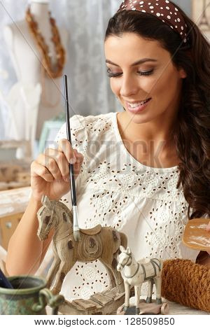 Happy young woman painting wooden horse in vintage style.